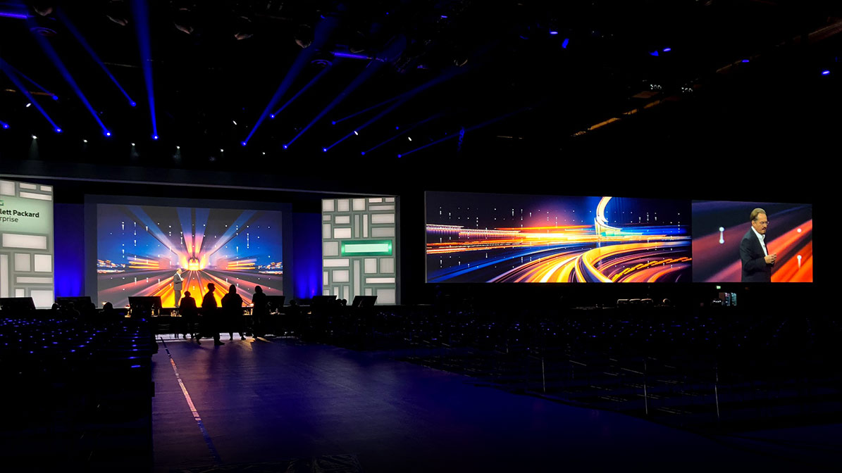 HPE Discover stage with colorful screens in the background