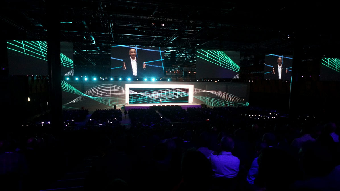Shot of presenter on huge HPE Discover screens with audience in the foreground