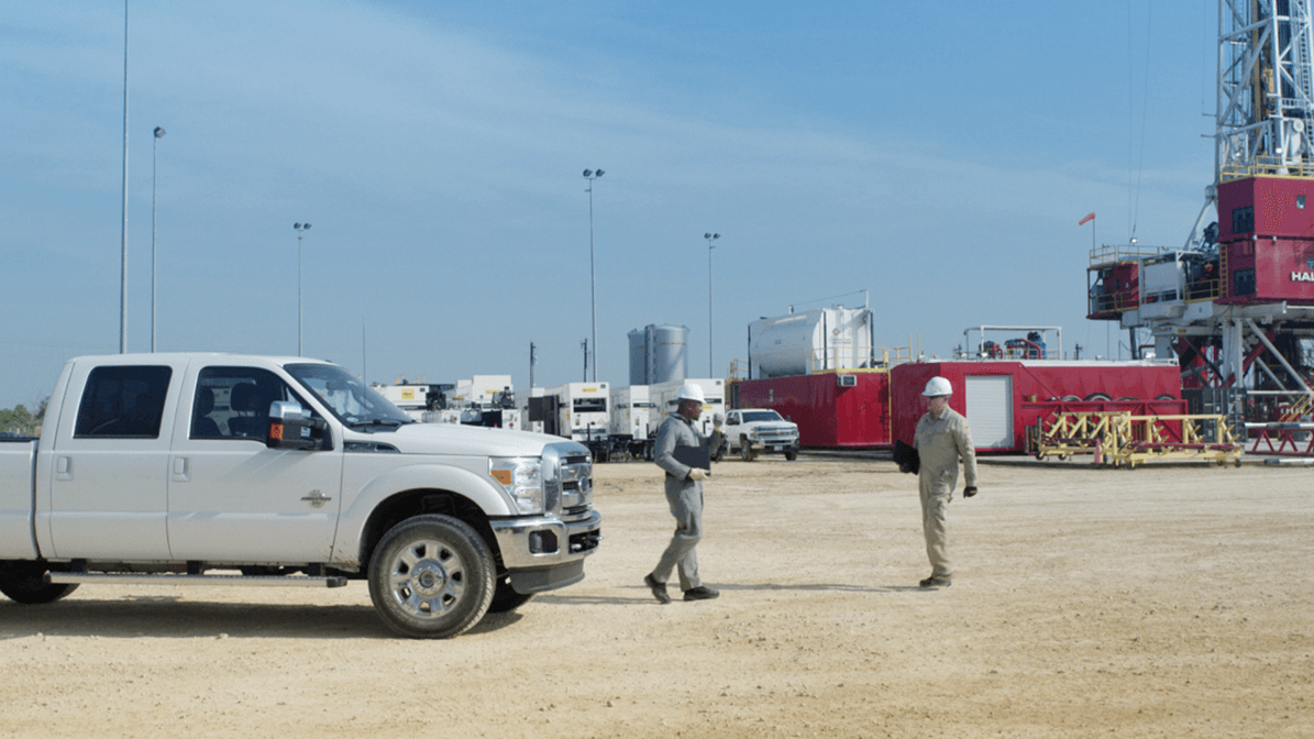 Two Halliburton team members out in the field with a pickup truck next to them
