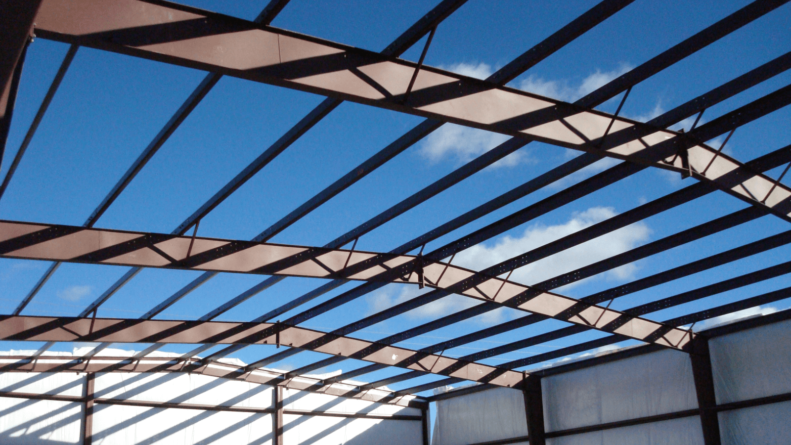Picture of bare roof beams against a clear blue sky