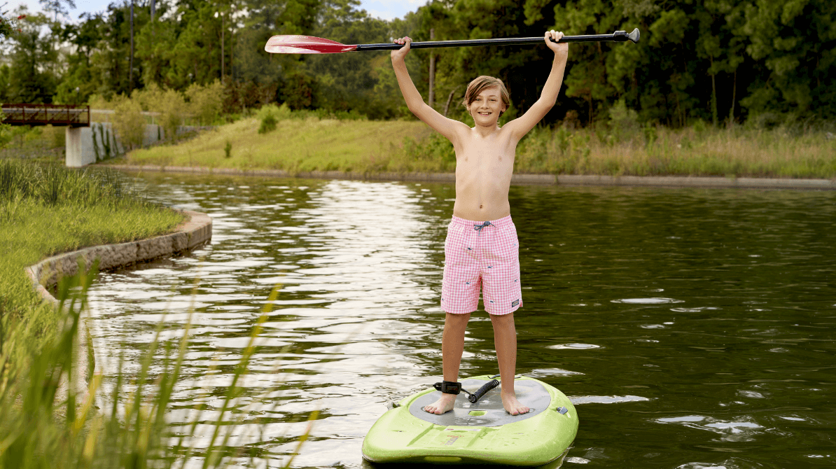 Child paddleboarding on the Woodlands river